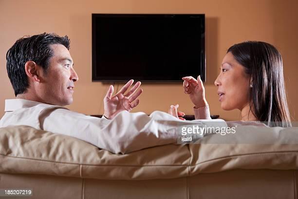 Asian couple watching TV, talking