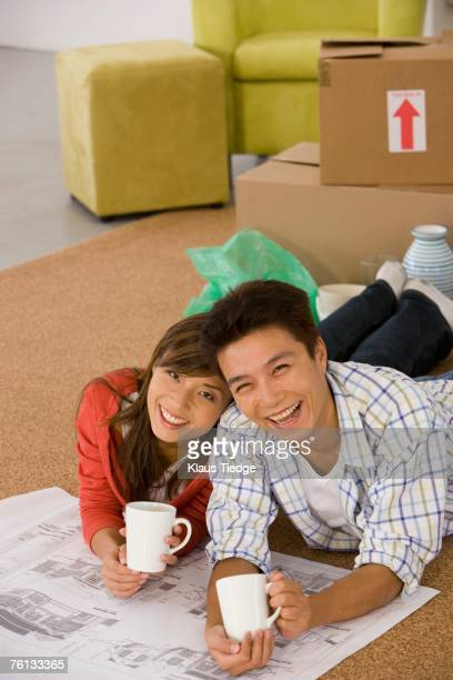 Asian couple with blueprints in new house