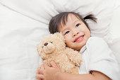 Asian cute little child girl hugging teddy bear in bed