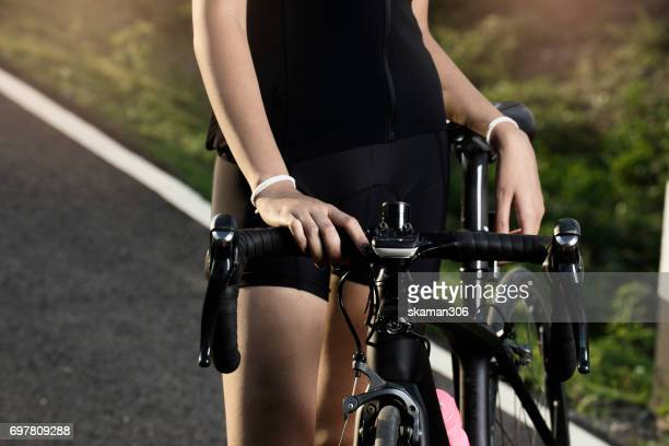 Asian Cyclist Girl exercise and holding handle Cycling on country side road by road bike (Bicycle ) sport and wellness concept
