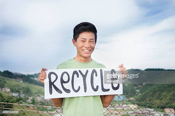 Asian descent teenage boy holds 'recycle' sign outdoors.