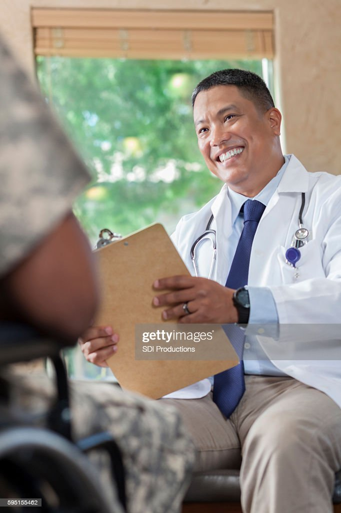 Asian doctor counseling young soldier during appointment