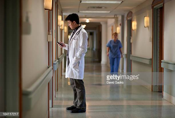 Asian doctor in hospital corridor with phone