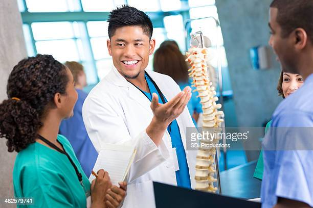 Asian doctor teaching medical interns with spine model in class