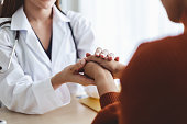 Asian doctor woman encourage young woman patient by holding hand