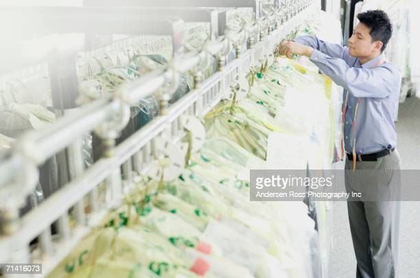 Asian drycleaner checking clothes