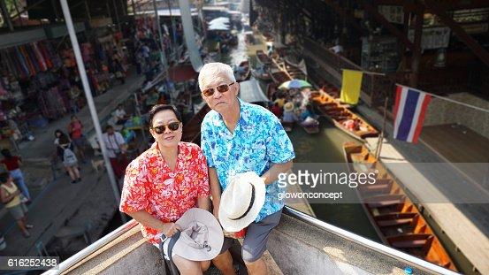 Asian elderly couple having retirement trip to Thailand floating : Stock Photo