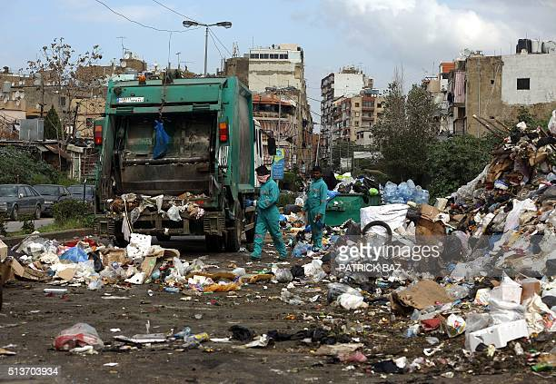 Asian employees from Sukleen a local trash management company collect garbage from a temporary garbage dump in an eastern suburb of the Lebanese...