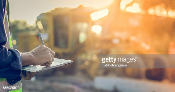 Asian engineer with hardhat using  tablet pc computer inspecting and working at construction site : Stock Photo