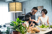 Happy young Asian family cooking together in the kitchen at home.