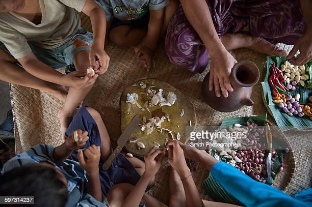 Asian family eating on woven mat