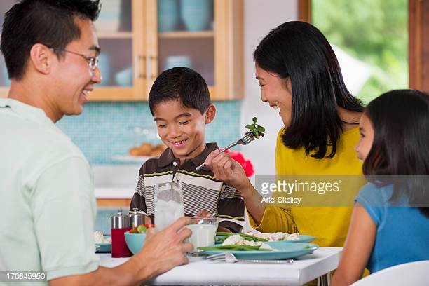 Asian family eating together at table