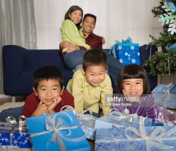 Asian family in living room with Christmas gifts