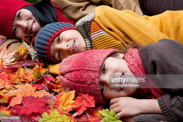 Asian family laying on autumn leaves