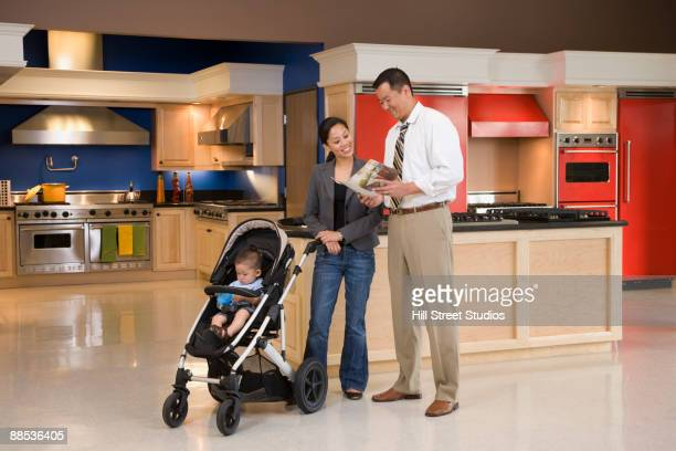 Asian family looking at brochure in kitchen showroom