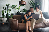 Young Asian family using the laptop and spending time together at home.