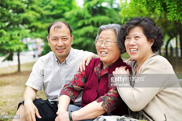 Asian family of three laughing and enjoying the park