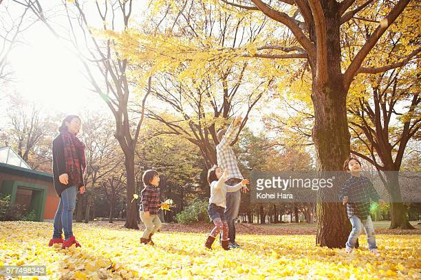 asian family playing in the park in autumn