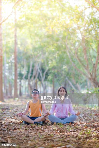 Asian family practicing yoga outdoor at public park