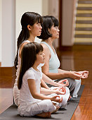 Asian family practicing yoga