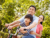 mother father and son riding a bicycle together outdoors in a city park.