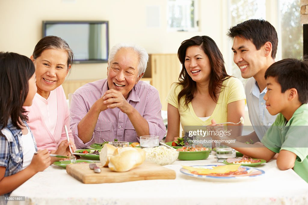 Asian family sharing meal at home : Stock Photo