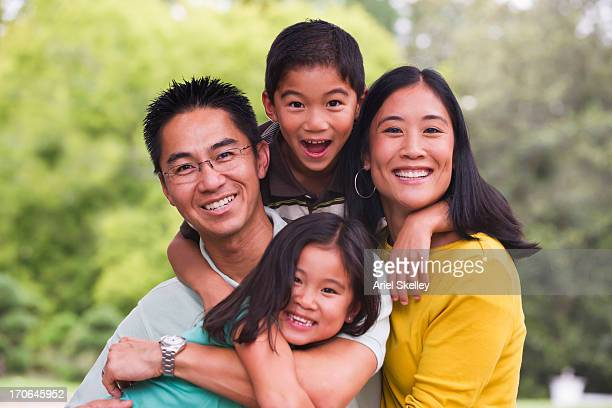 Asian family smiling together outdoors