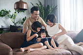 Young Asian family using a tablet in the living room.