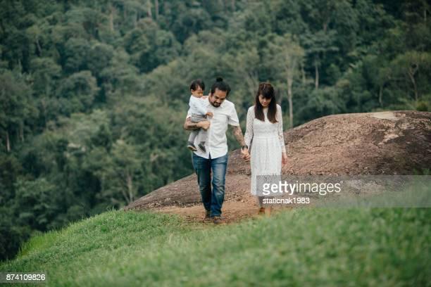 Asiatischen Familie Wandern auf grünen Hügel