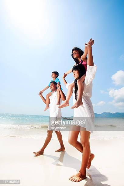 Asiatische Familie zu Fuß auf den Strand.