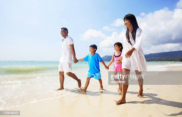 Asian family walking on the beach.