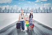Asian family wearing Santa hat while walking together on the snowy road with suitcases