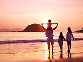 asian family standing on beach watching and enjoying the sunrise.