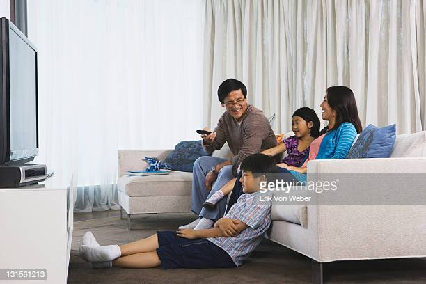 Asian family watching tv in their home