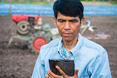 Asian farmer using tablet in agriculture farm with cultivate machine in background