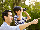 asian father and son using binoculars in park