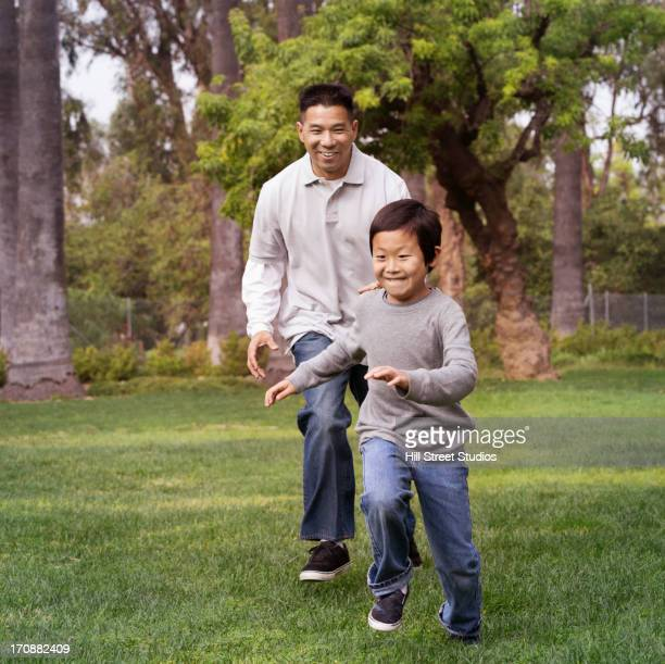 Asian father and son playing outdoors