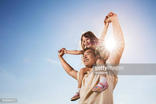 Asian father carrying daughter on shoulders against the blue sky.