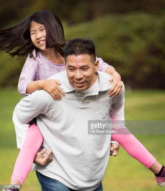 Asian father carrying daughter outdoors