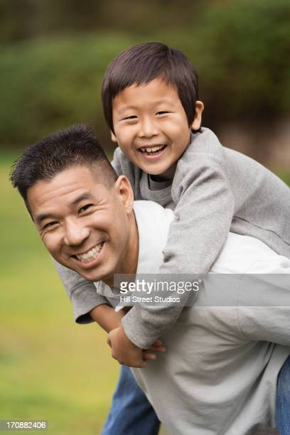 Asian father carrying son outdoors