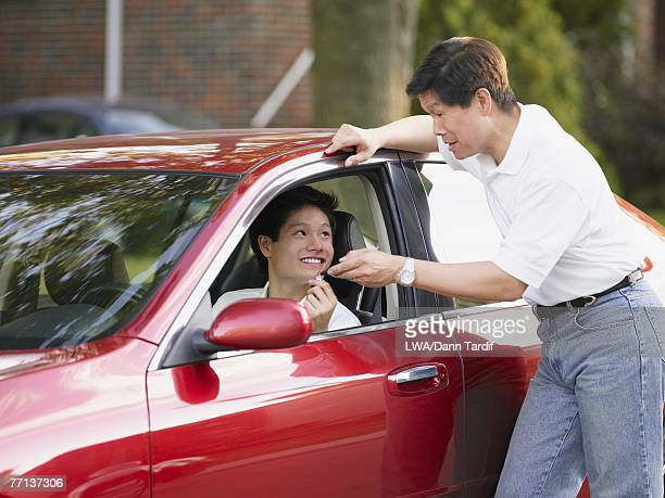Asian father handing car keys to son