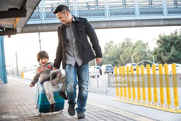 Asian Father Pulls Son on Suitcase Waiting for the Train