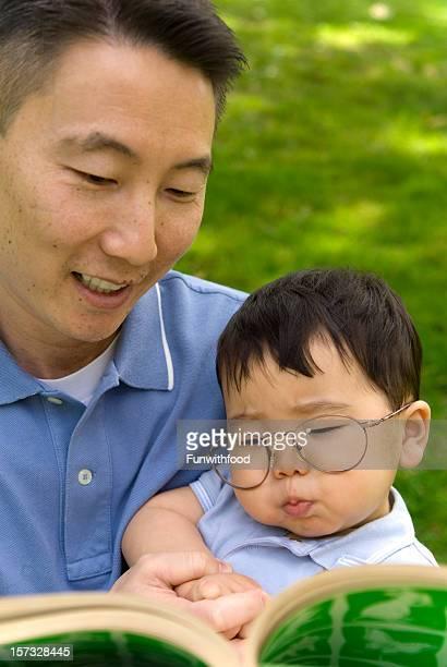 Père lisant à bébé asiatique coréen enfant famille heureuse ensemble