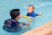 Asian Father take Cute little Asian 18 months / 1 year old toddler baby boy child to swimming class in Thailand, Happy infant enjoying his first swim in pool with his dad, Selective focus