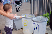 Asian father teach 18 months, 1 year old toddler baby boy child throwing plastic bottle in recycling trash bin at public place, Eco friendly Save the world concept, Selective focus at kid's hand