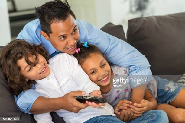 Asian Father Watching TV With Children