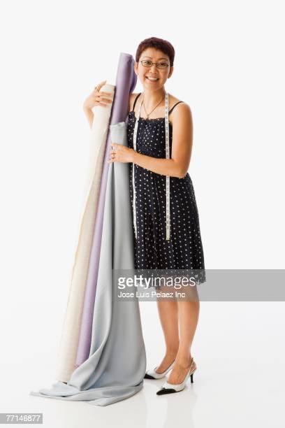 Asian female clothing designer holding rolls of fabric