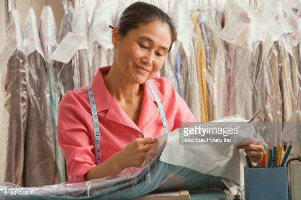 Asian female dry cleaner checking ticket