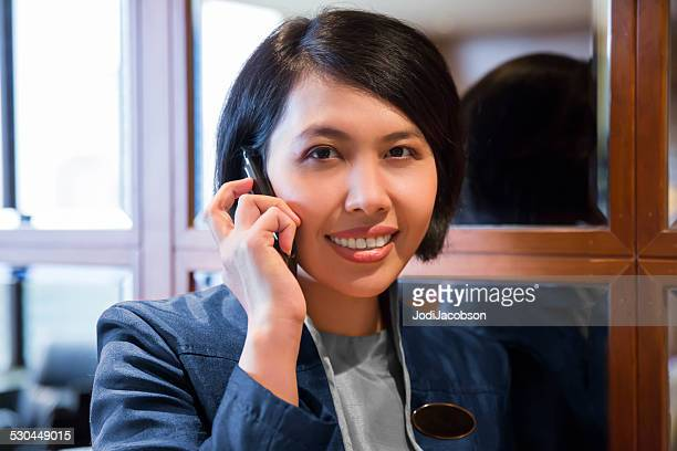 Asian female hotel concierge talking on her cell phone