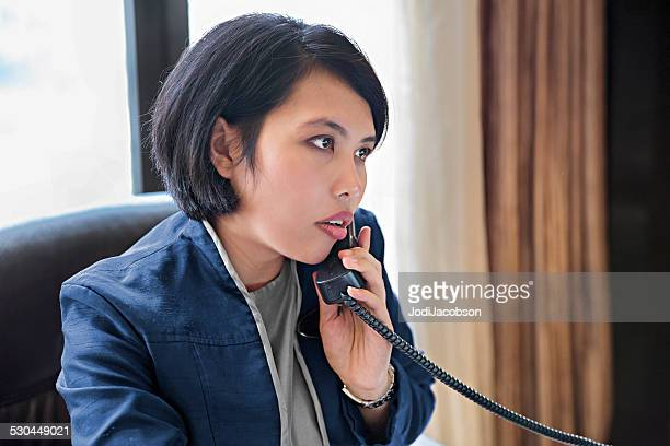 Asian female hotel concierge working at her desk